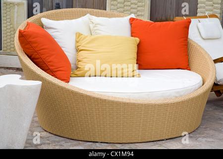A modern wicker garden sofa in the home garden. - Stock Photo