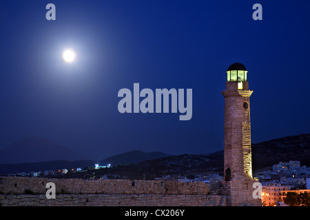 The lighthouse of the old Venetian harbor of Rethymno town under the full moon, around the 'blue' hour. Crete island, - Stock Photo