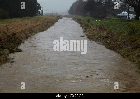 Silver Stream in flood, Mosgiel, Dunedin, Otago, South Island, New Zealand - Stock Photo