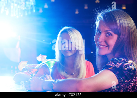 Portrait of happy girlfriends holding martini glasses with cocktails in bar - Stock Photo