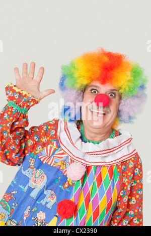 Portrait of cheerful senior male clown waving hand over gray background - Stock Photo