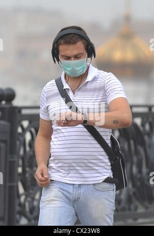 ITAR-TASS: MOSCOW, RUSSIA. AUGUST 4, 2010. Young man wearing a face mask and headphones looks at his wrist watch - Stock Photo