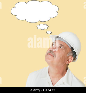 Senior construction worker with hardhat looking up over yellow background - Stock Photo