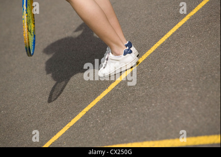 Tennis court, racket and shoes, heel on the line - Stock Photo
