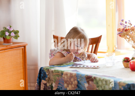 Little girl painting picture with watercolour - Stock Photo