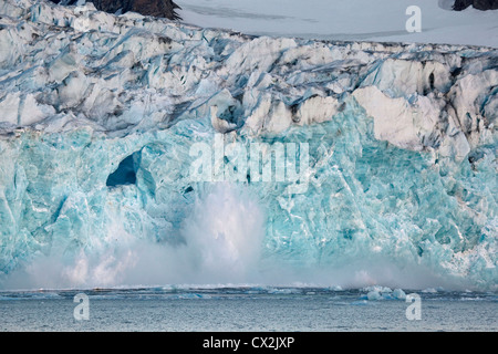 Large chunk of ice breaking off glacier and tumbling with big splash in the Magdalenefjord on Svalbard, Spitsbergen, - Stock Photo