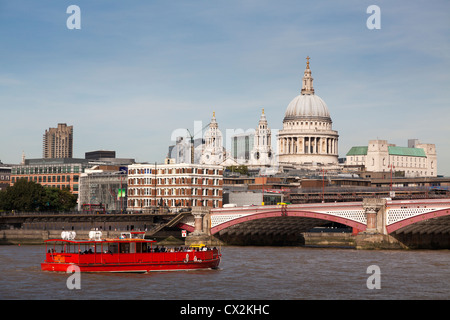 Red river crusier on the River Thames and Saint Paul's Cathedral Dome. - Stock Photo