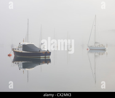 Boats in the mist on Kingsbridge Estuary, Salcombe, South Hams, Devon, England. Autumn (September) 2010. - Stock Photo