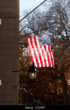 Flag of the USA over the John Harvard Statue in Harvard Yard, the old heart of the Harvard University campus in - Stock Photo