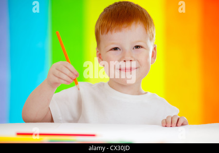 Red-haired adorable boy drawing with orange pencil on rainbow background - Stock Photo
