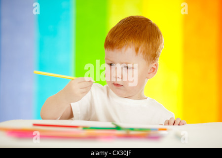 Redheaded adorable boy drawing with yellow pencil on rainbow background - Stock Photo