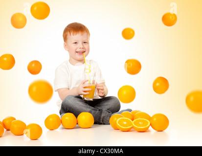 redheaded boy with falling oranges and orange juice - Stock Photo