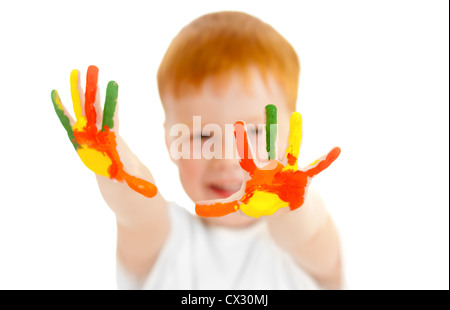 Adorable redheaded boy with focus on hands painted in bright colors - Stock Photo