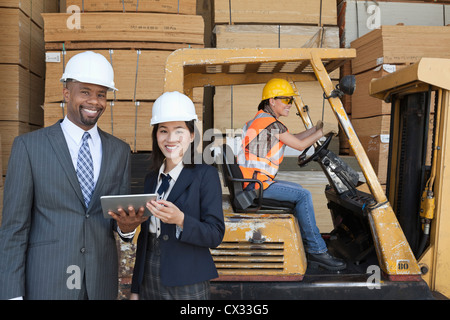 Happy multiethnic engineers holding tablet PC with female worker driving forklift truck in background - Stock Photo