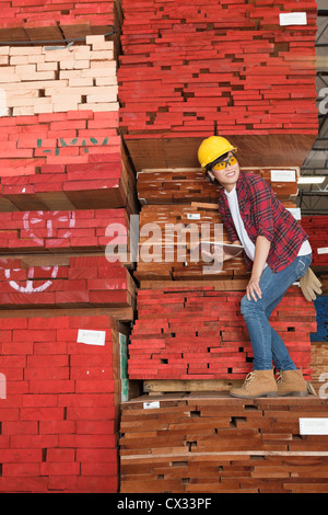 Asian female industrial worker standing on stacked wooden planks holding tablet PC - Stock Photo