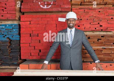 Portrait of happy African American male contractor standing in front of stacked wooden planks - Stock Photo
