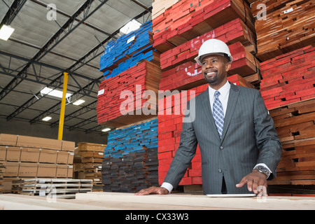 An African American male contractor standing in front of stacked wooden planks - Stock Photo