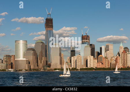 Sailboats catch the breeze on the Hudson River on a summer afternoon in front of the lower Manhattan skyline in - Stock Photo