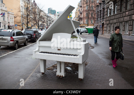 Pedestrians pass a white grand piano monument in downtown Kiev, Ukraine, Eastern Europe - Stock Photo
