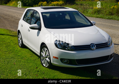New white compact diesel car with sunroof parked on a country road - Stock Photo