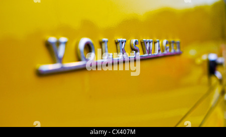 Macro of the Volkswagen badge on a bright yellow VW camper at the Dunstable Dubbers meet. - Stock Photo