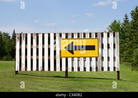 Directional arrow sign on a white fence. - Stock Photo