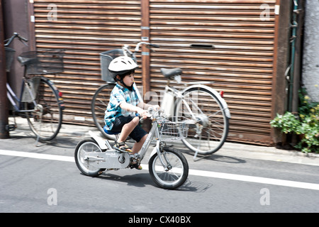 Young Japanese boy rides his fast bike on an urban street wearing helmet. - Stock Photo