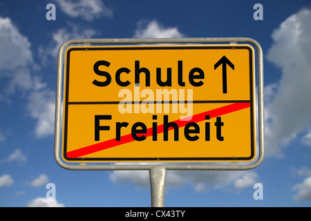 German road sign freedom and school with blue sky and white clouds - Stock Photo