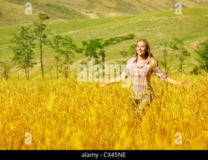 Photo of pretty woman running on golden wheat field, beautiful young lady having fun outdoors, happy smiling girl - Stock Photo