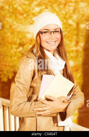 Image of beautiful student girl holding textbooks in autumn park, pretty cheerful teen female enjoying education - Stock Photo