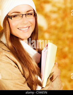 Image of cheerful student girl spend leisure in autumn park, closeup portrait of beautiful teen hold textbook in - Stock Photo
