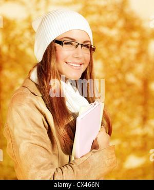 Closeup portrait of pretty student girl in autumn park, adult schoolgirl enjoying education, beautiful teen holding - Stock Photo