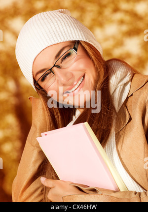 Photo of pretty student girl in autumn park and wearing beige leather coat with white warm hat, closeup portrait - Stock Photo