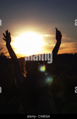 Young girl with hands up surrounding the sun at sunset - Stock Photo