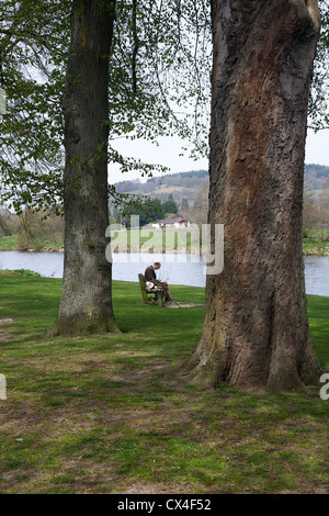 Old man on a bench at Builth Wells, Powys, Wales, UK - Stock Photo