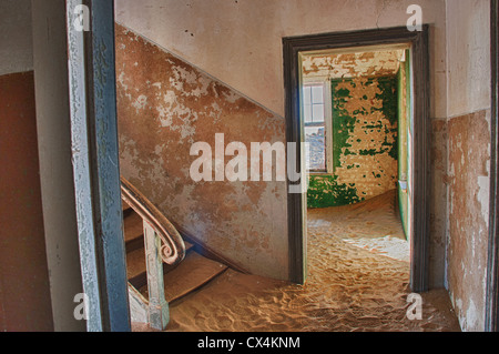 Interior room in Kolmanskop, a ghost mining town in Namibia, Africa. The desert has reclaimed the town after it - Stock Photo