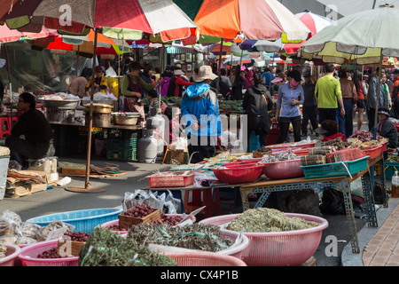 Colorful umbrellas and street vendors in the open air market in Jinhae, South Korea - Stock Photo