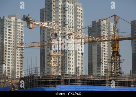 Construction cranes build high rise apartments in South Korea - Stock Photo