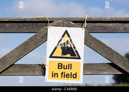 Bull in field warning sign on a wooden gate. - Stock Photo