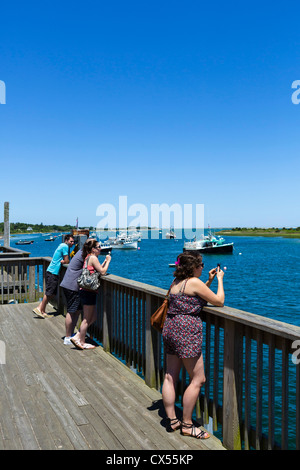 Tourists taking pictures from terrace overlooking the fishing harbour in Chatham, Cape Cod, Massachusetts, USA - Stock Photo