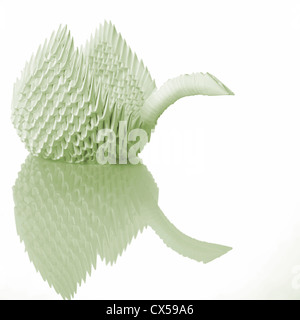 Origami art swan on table with reflection - Stock Photo