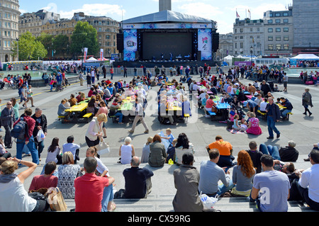 Picnic Tables placed in Trafalgar Square in front of large TV screen and stage during London 2012 Olympic and Paralympic - Stock Photo