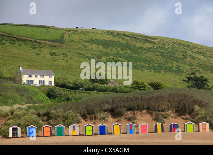 Row of brightly coloured beach huts with white house on grassy hill behind and cows on the horizon. - Stock Photo