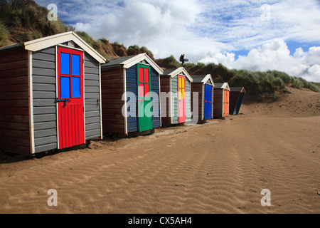 Brightly coloured beach huts with surfer silhouetted on horizon - Stock Photo