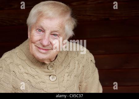 Happy senior lady in beige sweater smiling - Stock Photo