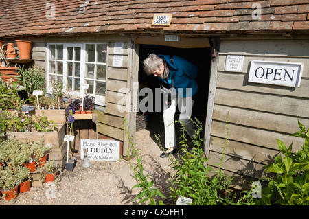 Nursery Plant Shop with low doorway and sign over saying 'Duck or Grouse' - at Great Dixter Garden, Sussex, UK. - Stock Photo