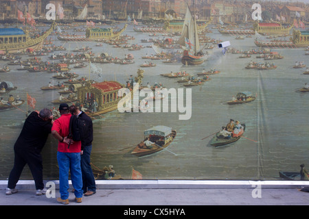 CCTV camera watches men peeling the background of Canaletto's 18th century painting of the Lord Mayor's Show regatta - Stock Photo