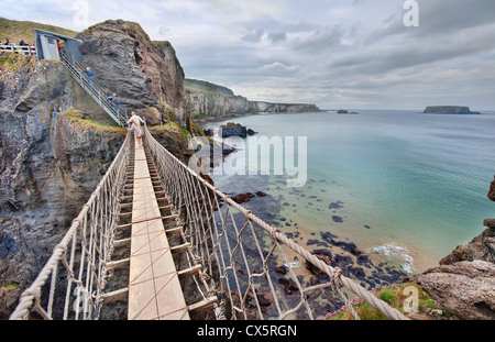 The Carrick-a-Rede Rope Bridge spans two cliff faces in County Antrim on the coast of Northern Ireland, near the - Stock Photo