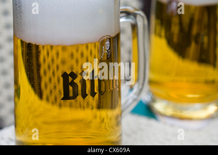 Two glasses of German Bitburger beer on a table - Stock Photo