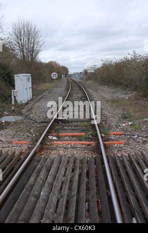 an empty train track on a foot crossing leading into the distance - Stock Photo
